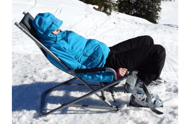A man with a blue jacket relaxing on a chair on a snowy mountain.